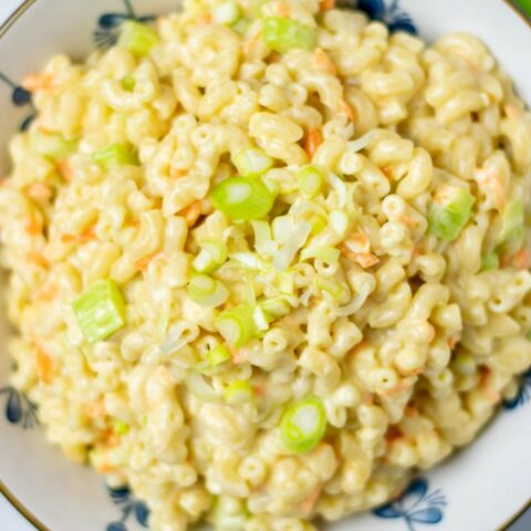 Top view on the Hawaiian Macaroni Salad in a large bowl, with creamy dressing, and the vegetable ingredients visible.