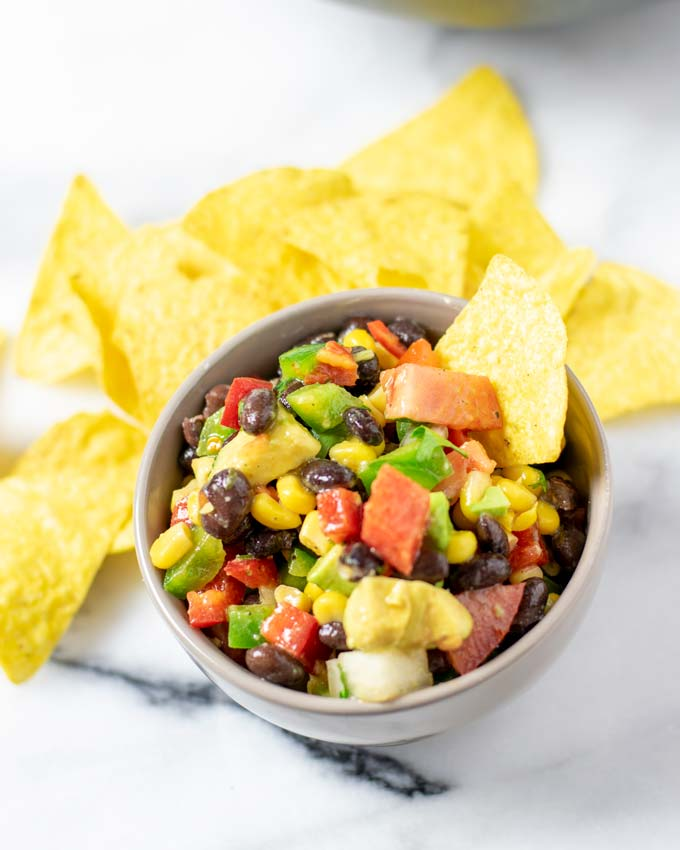 A portion of the Cowboy Caviar in a small bowl with tortilla chips.