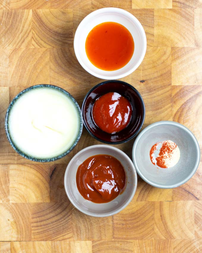 Ingredients needed for making this homemade Boom Boom Sauce assembled on a wooded board.
