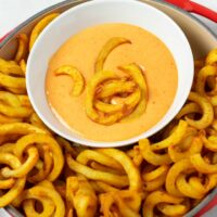 Some fries are given into the bowl with the Boom Boom Sauce.