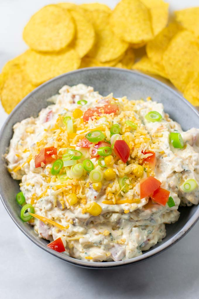 The Fiesta Ranch Dip in a serving bowl, topped with extra vegan cheese, tomatoes and scallions. Some Nacho Chips in the background.