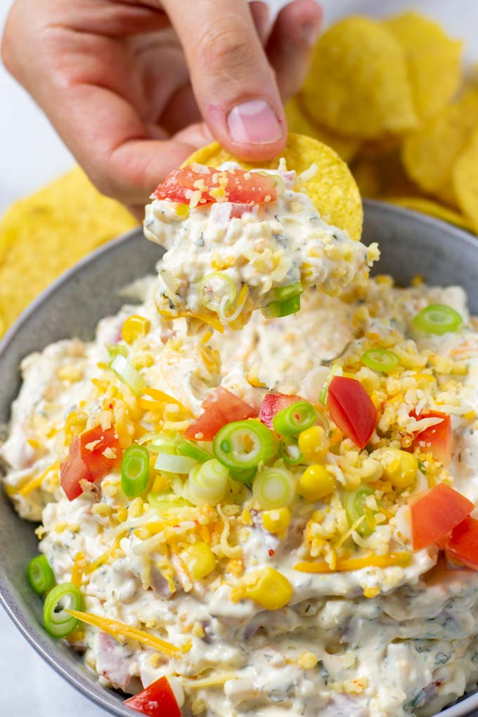 A hand is holding a nacho chip that has been dipped into the Fiesta Ranch Dip.