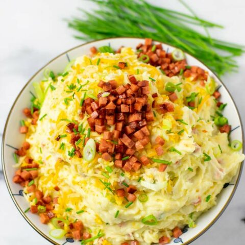 A large serving bowl of the Loaded Mashed Potatoes, topped with extra vegan bacon, cheese, and scallions.
