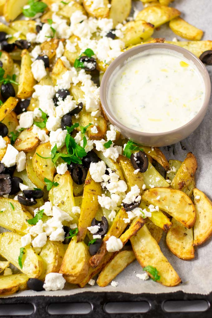 Baking sheet with the ready Greek Fries and a small bowl of homemade Tzatziki sauce for dipping.