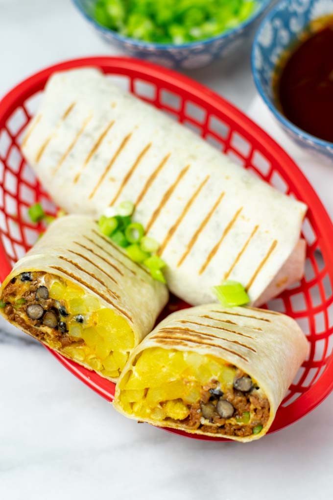 A red basket with one closed and one open cup French Taco revealing the filling.