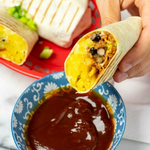A half French Taco is held in one hand over a small bowl with dipping sauce.