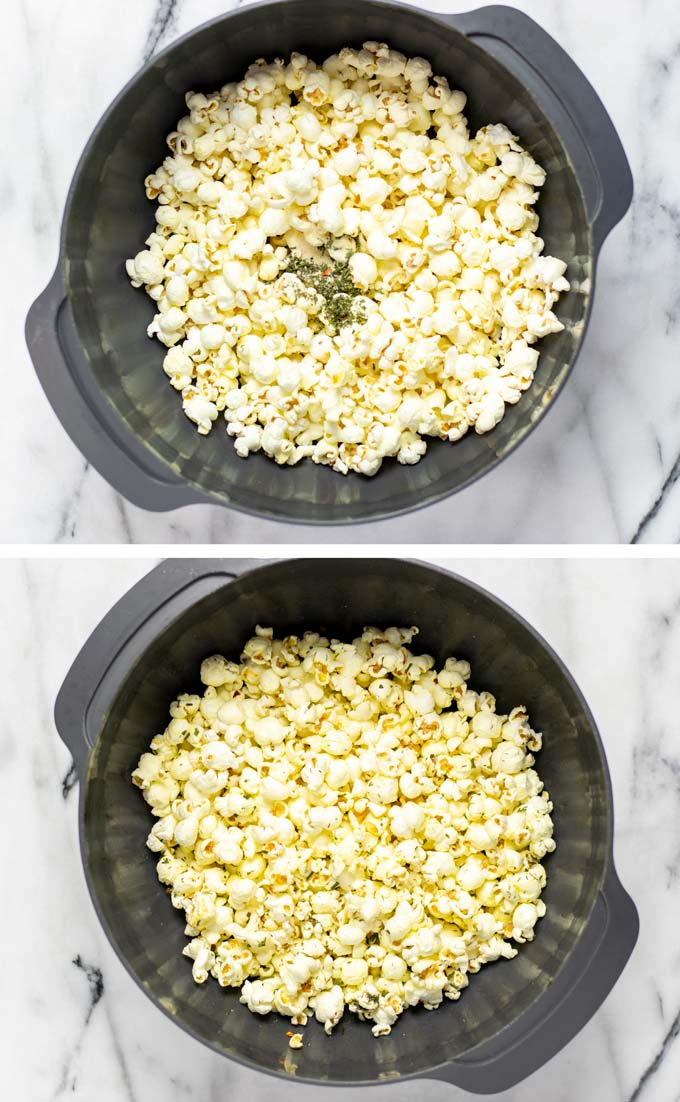 Popcorn is mixed with oil and spices in a large mixing bowl.