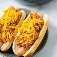 A plate with two hot dogs loaded with the Hot Dog Chili and sprinkled with vegan cheese.